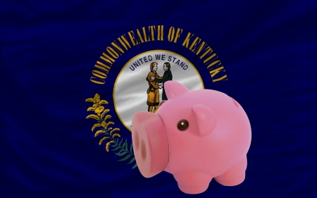 accumulating: Piggy rich bank in front of flag of us state of kentucky symbolizing saving and accumulating funds as good financial habit
