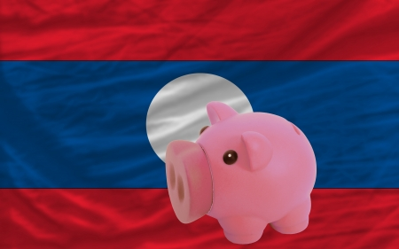 accumulating: Piggy rich bank in front of national flag of laos symbolizing saving and accumulating funds as good financial habit