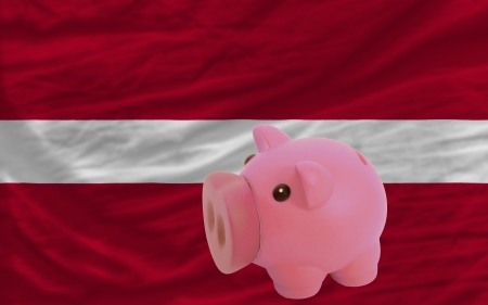 Piggy rich bank in front of national flag of latvia symbolizing saving and accumulating funds as good financial habit photo