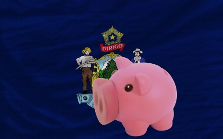 accumulating: Piggy rich bank in front of flag of us state of maine symbolizing saving and accumulating funds as good financial habit