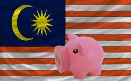 piktogramm: Piggy rich bank in front of national flag of malaysia symbolizing saving and accumulating funds as good financial habit