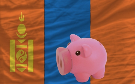 accumulating: Piggy rich bank in front of national flag of mongolia symbolizing saving and accumulating funds as good financial habit