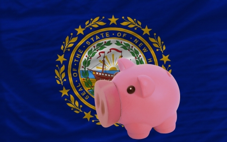 accumulating: Piggy rich bank in front of flag of us state of new hampshire symbolizing saving and accumulating funds as good financial habit Stock Photo