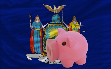 accumulating: Piggy rich bank in front of flag of us state of new york symbolizing saving and accumulating funds as good financial habit
