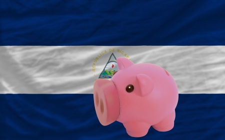 piktogramm: Piggy rich bank in front of national flag of nicaragua symbolizing saving and accumulating funds as good financial habit