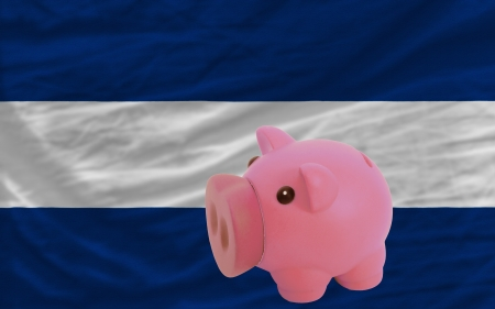 accumulating: Piggy rich bank in front of national flag of nicaragua symbolizing saving and accumulating funds as good financial habit