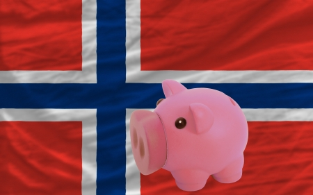 piktogramm: Piggy rich bank in front of national flag of norway symbolizing saving and accumulating funds as good financial habit Stock Photo