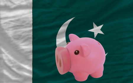 accumulating: Piggy rich bank in front of national flag of pakistan symbolizing saving and accumulating funds as good financial habit