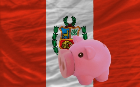 Piggy rich bank in front of national flag of peru symbolizing saving and accumulating funds as good financial habit photo