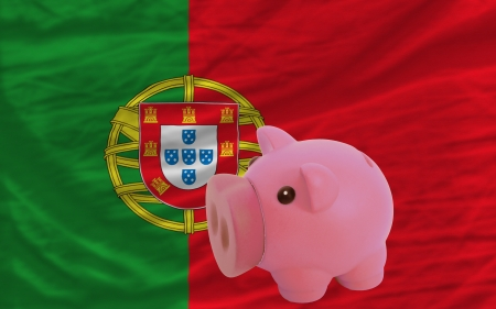 Piggy rich bank in front of national flag of portugal symbolizing saving and accumulating funds as good financial habit photo