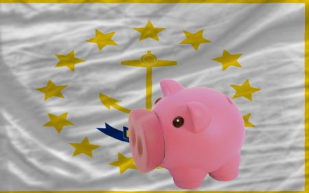 accumulating: Piggy rich bank in front of flag of us state of rhode island symbolizing saving and accumulating funds as good financial habit