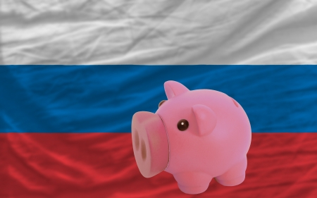 accumulating: Piggy rich bank in front of national flag of russia symbolizing saving and accumulating funds as good financial habit