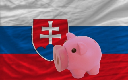 accumulating: Piggy rich bank in front of national flag of slovakia symbolizing saving and accumulating funds as good financial habit
