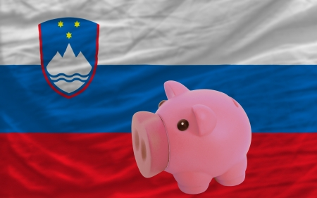 piktogramm: Piggy rich bank in front of national flag of slovenia symbolizing saving and accumulating funds as good financial habit Stock Photo