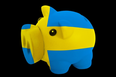 piggy rich bank in colorsnational flag of swedenfor saving money on black background photo