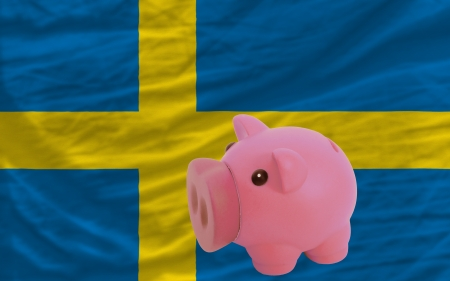 Piggy rich bank in front of national flag of sweden symbolizing saving and accumulating funds as good financial habit photo