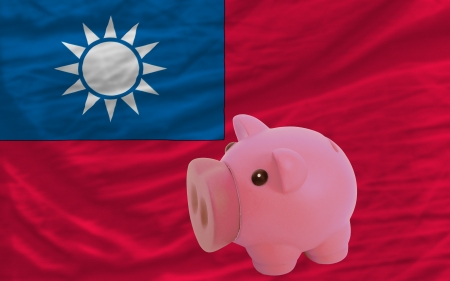 accumulating: Piggy rich bank in front of national flag of taiwan symbolizing saving and accumulating funds as good financial habit
