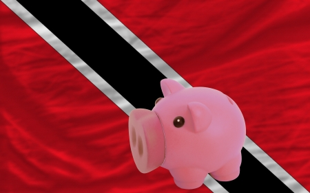 national flag trinidad and tobago: Piggy rich bank in front of national flag of trinidad tobago symbolizing saving and accumulating funds as good financial habit