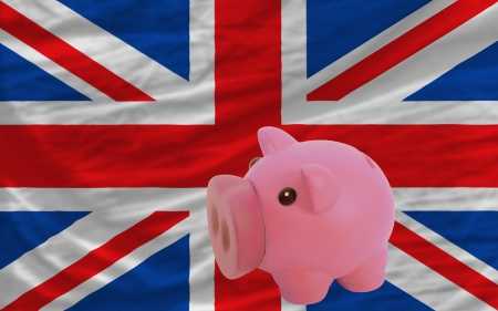 Piggy rich bank in front of national flag of uk symbolizing saving and accumulating funds as good financial habit photo