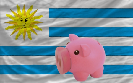 piktogramm: Piggy rich bank in front of national flag of uruguay symbolizing saving and accumulating funds as good financial habit Stock Photo