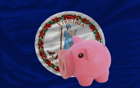 accumulating: Piggy rich bank in front of flag of us state of virginia symbolizing saving and accumulating funds as good financial habit