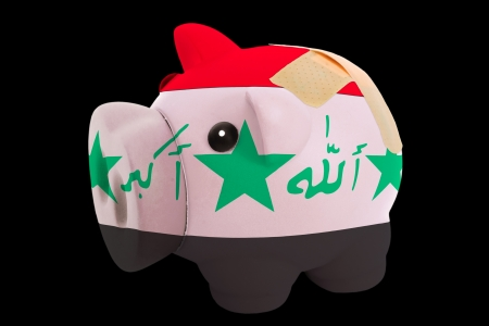 iraq money: empty piggy rich bank in colors of national flag of iraq on black background