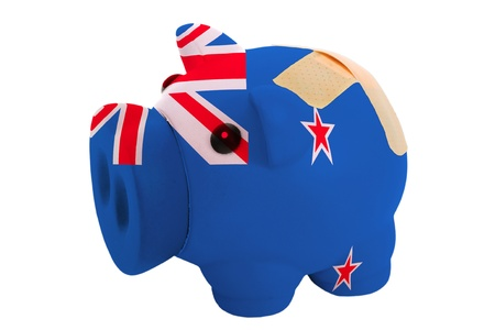 epty poor man piggy rich bank in colorsnational flag of new zealand on white photo