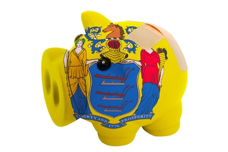epty poor man piggy rich bank in colorsflag of us state of new jersey on white photo