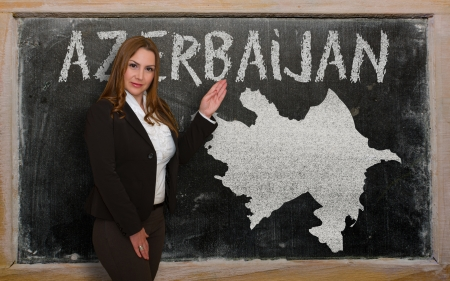 azerbaijani: Successful, beautiful and confident young woman showing map of azerbaijan on blackboard for presentation, marketing research and tourist advertising Stock Photo