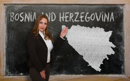 bosnia and  herzegovina: Successful, beautiful and confident young woman showing map of bosnia herzegovina on blackboard for presentation, marketing research and tourist advertising