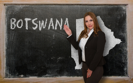 botswanan: Successful, beautiful and confident young woman showing map of botswana on blackboard for presentation, marketing research and tourist advertising