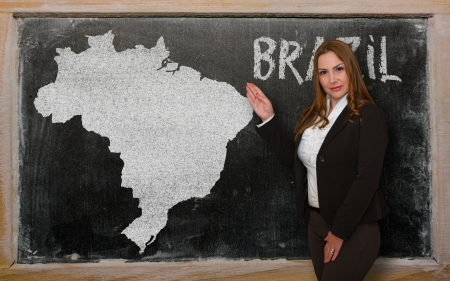 Successful, beautiful and confident young woman showing map of brazil on blackboard for presentation, marketing research and tourist advertising photo