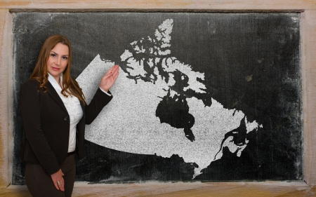 Successful, beautiful and confident young woman showing map of canada on blackboard for presentation, marketing research and tourist advertising photo