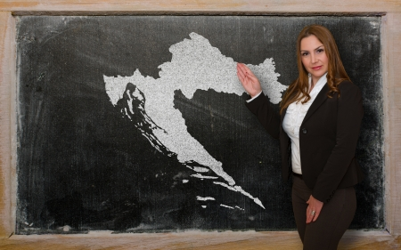 Successful, beautiful and confident young woman showing map of croatia on blackboard for presentation, marketing research and tourist advertising photo