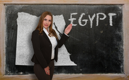 Successful, beautiful and confident young woman showing map of egypt on blackboard for presentation, marketing research and tourist advertising photo