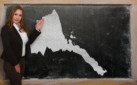 Successful, beautiful and confident young woman showing map of eritrea on blackboard for presentation, marketing research and tourist advertising photo