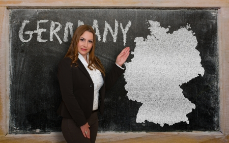 Successful, beautiful and confident young woman showing map of germany on blackboard for presentation, marketing research and tourist advertising photo