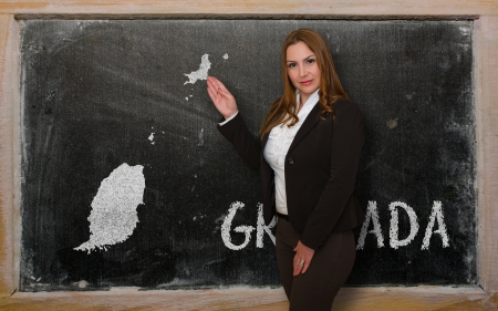 Successful, beautiful and confident young woman showing map of grenada on blackboard for presentation, marketing research and tourist advertising Stock Photo