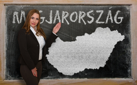 Successful, beautiful and confident young woman showing map of hungary on blackboard for presentation, marketing research and tourist advertising photo