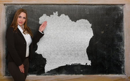 Successful, beautiful and confident young woman showing map of ivory coast on blackboard for presentation, marketing research and tourist advertising photo