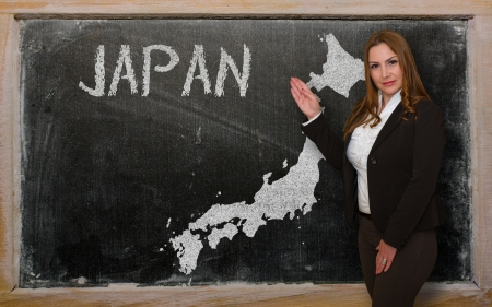 Successful, beautiful and confident young woman showing map of japan on blackboard for presentation, marketing research and tourist advertising photo