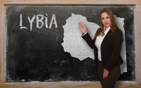 Successful, beautiful and confident young woman showing map of lybia on blackboard for presentation, marketing research and tourist advertising photo
