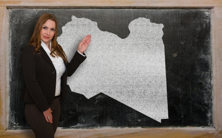 lybia: Successful, beautiful and confident young woman showing map of lybia on blackboard for presentation, marketing research and tourist advertising