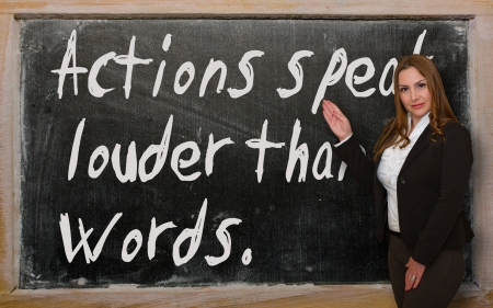 Successful, beautiful and confident woman showing Actions speak louder than words on blackboard