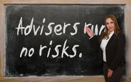 advisers: Successful, beautiful and confident woman showing Advisers run no risks on blackboard Stock Photo