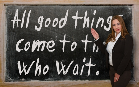 Successful, beautiful and confident woman showing All good things come to those who wait on blackboard