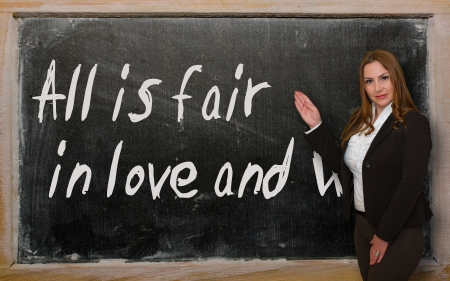 Successful, beautiful and confident woman showing All is fair in love and war on blackboard