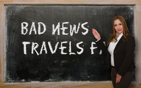 Successful, beautiful and confident woman showing Bad news travels fast on blackboard Stock Photo