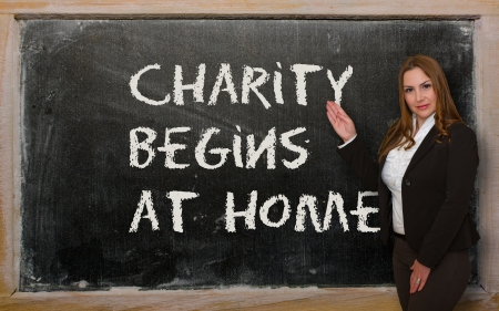 Successful, beautiful and confident woman showing Charity begins at home on blackboard