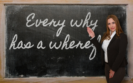 has: Successful, beautiful and confident woman showing Every why has a wherefore on blackboard Stock Photo